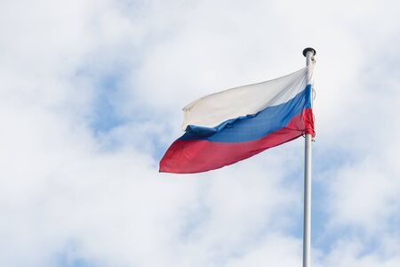 The Russian flag flies in the wind against the blue sky