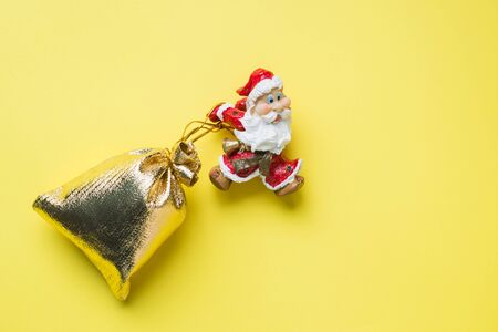 A toy Santa with a gold sack of gifts on yellow background with copy space. The concept of Christmas new year