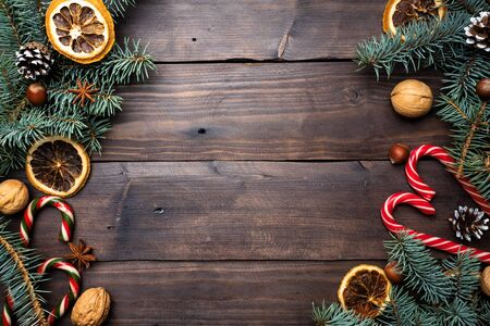 Frame of Christmas tree cones oranges caramel cane nuts on dark wooden background. Copy space. Flat lay Фото со стока