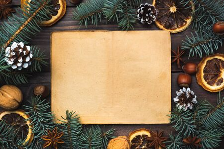 Frame of Christmas tree cones oranges nuts on dark wooden background. Copy space. Flat lay Old paper for text.