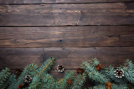 Christmas tree with cones on a dark wooden background. Copy space. Flat lay