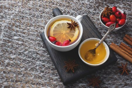 Drink from wild rose berries with lemon and honey cinnamon. Vitamin useful decoction of rose hips. cozy home concept of winter drink. Copy space