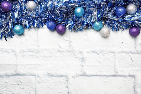 Christmas frame made of Christmas garland tinsel decorations in silver and blue on a light brick background. Copy space. Flat lay Фото со стока