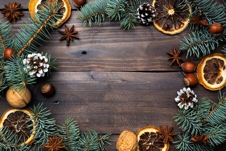 Frame of Christmas tree cones oranges nuts on dark wooden background. Copy space. Flat lay