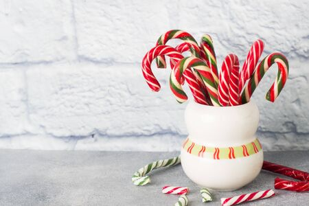 Lots of Christmas candy canes in a mug on a grey background with copy space. Bright festive Christmas caramel