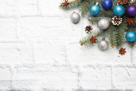 Christmas frame made of fir, Christmas tree decorations in silver and blue on a light brick background. Copy space. Flat lay