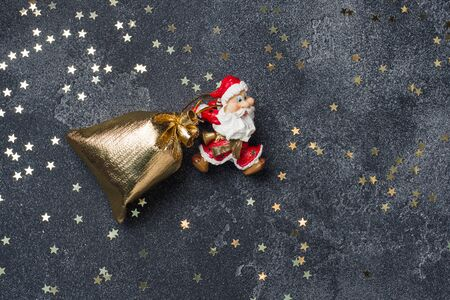 The concept of Christmas night. Santa drags a bag of gifts Dark star background. Copy space.