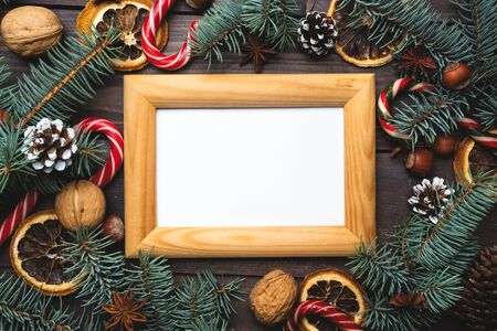 Frame of Christmas tree cones oranges caramel cane nuts on dark wooden background. Copy space. Flat lay Wooden frame and space for text. Фото со стока
