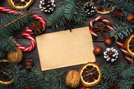 Frame of Christmas tree cones oranges caramel cane nuts on dark wooden background. Copy space. Flat lay Old paper for text.