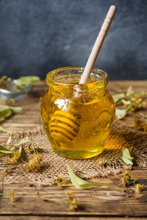 A jar of liquid honey from Linden flowers and a stick with honey on a dark background