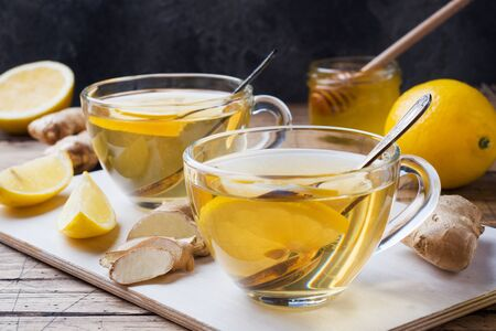 Two cups of natural herbal tea ginger lemon and honey on a wooden background Фото со стока