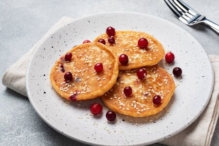 Cottage cheese pancakes with cranberries. Russian syrniki or sirniki, cottage cheese fritters or pancakes on the plate Фото со стока