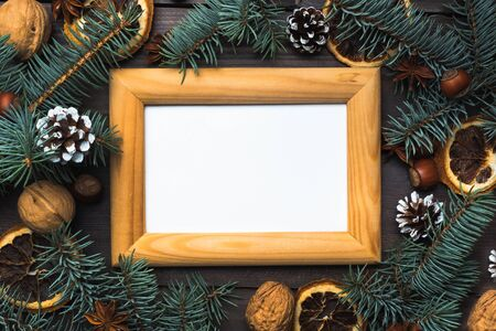 Frame of Christmas tree cones oranges nuts on dark wooden background. Copy space. Flat lay Wooden frame and space for text.
