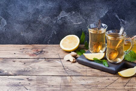 Two cups of natural herbal tea ginger lemon mint and honey on a wooden background Copy space Фото со стока