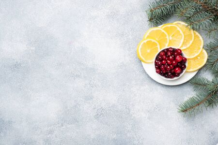 Fresh raw berries cranberries and lemon in a plate on a gray background with copy space