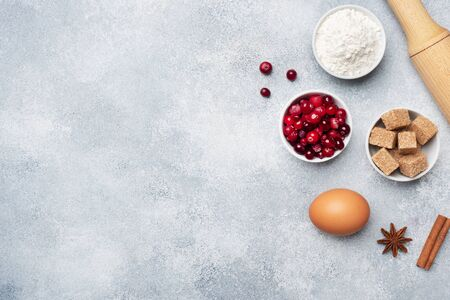 Ingredients for baking cookies, cupcakes and cake. Raw foods eggs flour sugar cranberries on a grey background with copy space