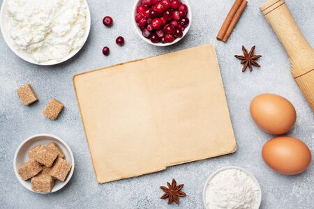 Ingredients for baking cookies, cupcakes and cake. Frame of Raw foods eggs flour sugar cottage cheese cranberries on a grey background with copy space