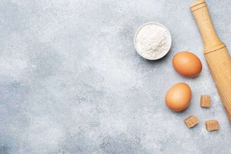 Ingredients for baking cookies, cupcakes and cake. Raw foods eggs flour sugar on a grey background with copy space Stok Fotoğraf