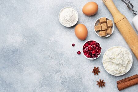 Ingredients for baking cookies, cupcakes and cake. Raw foods eggs flour sugar cottage cheese cranberries on a grey background with copy space Stok Fotoğraf