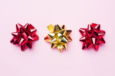 Gold and red Christmas bows on pink background. Gift concept greetings for holidays birthday Wedding New year Christmas mothers Day. Copy space