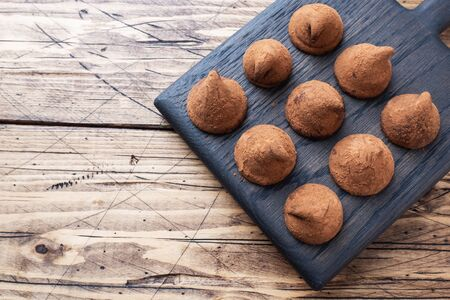 Delicious chocolate truffles sprinkled with cocoa powder on a wooden stand. Wooden background. Copy space