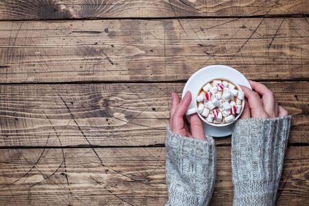 Female hands hold a Cup of hot chocolate and marshmallow on a wooden table. Copy space Winter cozy concept.