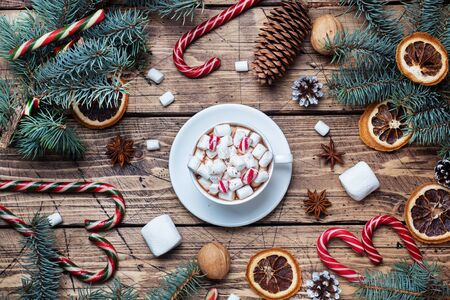A Cup of hot chocolate with marshmallows. Christmas tree and decorations, cane caramel and oranges nuts Wooden background.