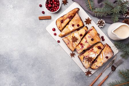 Cottage cheese pie casserole with cranberries and spices sprinkled with powdered sugar on a wooden stand. Gray concrete table Copy space Фото со стока