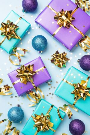 Flat lay background for celebration Christmas and New Year. Gift boxes are purple and turquoise with gold ribbons bows and confetti stars on a blue background. top view.