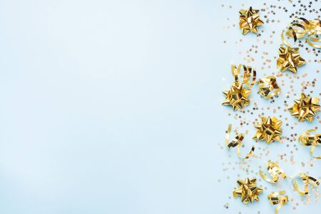 Flat lay background for celebration Christmas and New Year. gold ribbons bows and confetti stars on a blue background. top view copy space Фото со стока