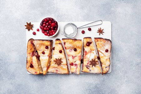 Cottage cheese pie casserole with cranberries and spices sprinkled with powdered sugar on a wooden stand. Gray concrete table Copy space Stock Photo