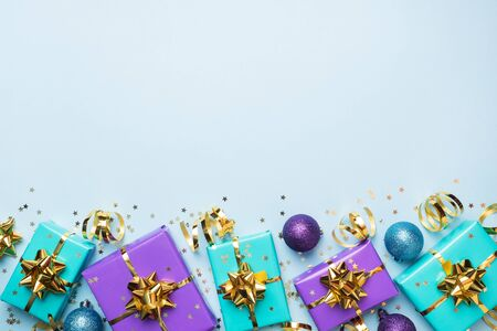 Flat lay background for celebration Christmas and New Year. Gift boxes are purple and turquoise with gold ribbons bows and confetti stars on a blue background. top view copy space