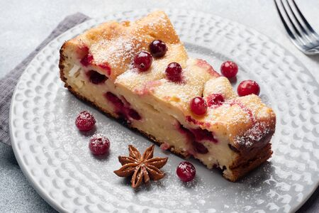 A piece of cottage cheese pie casserole with cranberry berries and spices cinnamon and anise on a plate. Grey concrete background
