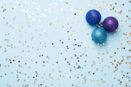 Flat lay background for celebration Christmas and New Year. Balls are purple and turquoise with gold ribbons bows and confetti stars on a blue background. top view copy space Фото со стока