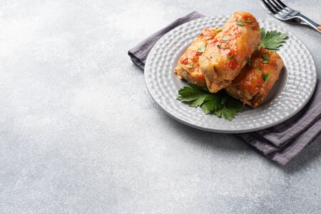 Cabbage rolls with beef, rice and vegetables on the plate. Stuffed cabbage leaves with meat. Gray concrete table Copy space Фото со стока