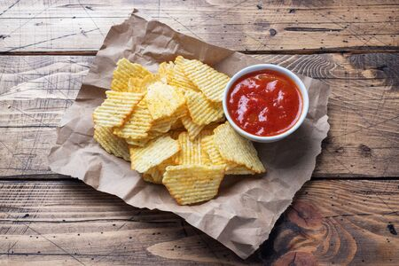 Spiced potato chips on paper and a plate of ketchup sauce on a wooden table copy space.