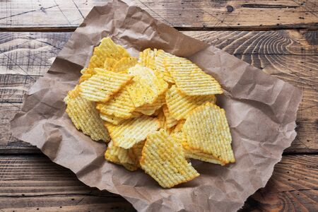 Potato fluted chips with spices on paper on a wooden table