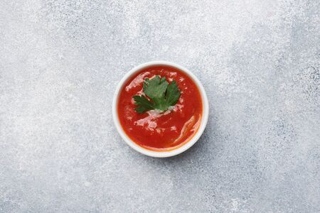 Ketchup greens in plates on a gray concrete table with copy space Фото со стока