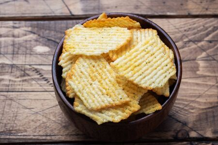 Potato fluted chips with spices in a wooden bowl on a wooden table copy space.