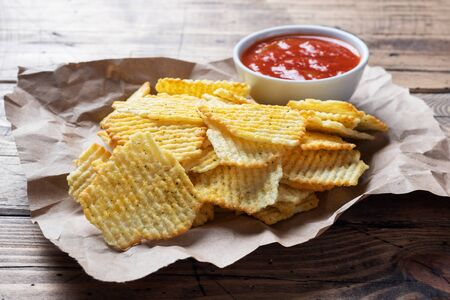 Spiced potato chips on paper and a plate of ketchup sauce on a wooden table Фото со стока