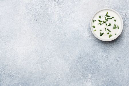 mayonnaise greens in plates on a gray concrete table with copy space