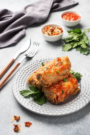 Cabbage rolls with beef, rice and vegetables on the plate. Stuffed cabbage leaves with meat. Gray concrete table.