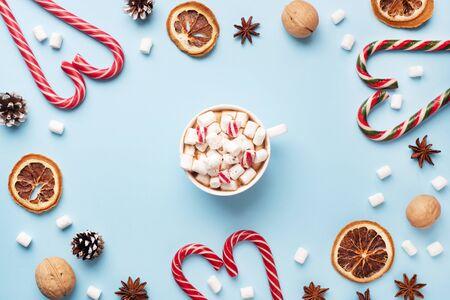 Tasse heiße Schokolade mit Marshmallow-Kakaopulver und Karamellnüssen, Orangen auf pastellblauem Hintergrund mit Kopierraum. Weihnachtswinterkonzept Standard-Bild