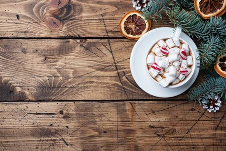 A Cup of hot chocolate with marshmallows. Christmas tree and decorations, cane caramel and oranges nuts Wooden background copy space