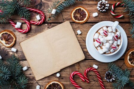 A Cup of hot chocolate with marshmallow in the hands of a man in a sweater. Christmas tree and decorations, cane caramel and oranges nuts Wooden background copy space. New year gift