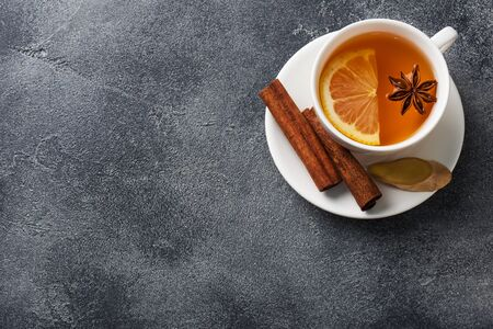 White Cup with natural herbal tea with lemon cinnamon. Hot vitamin drink is used for colds.Dark concrete background copy space