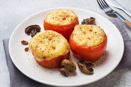 Baked whole tomatoes stuffed with mushrooms and cheese with spices on a light concrete background
