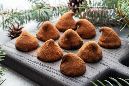 Delicious chocolate truffles sprinkled with cocoa powder on a wooden stand. Christmas tree scenery concept Фото со стока