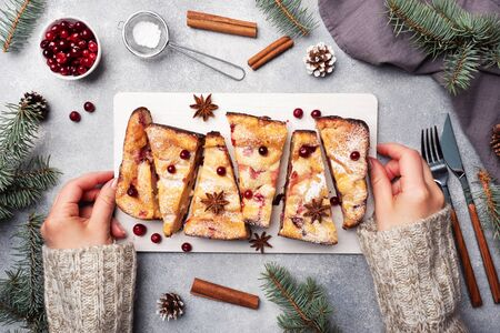 Female hands hold a stand with a Cottage cheese pie casserole with cranberries and spices sprinkled with powdered sugar. Gray concrete table