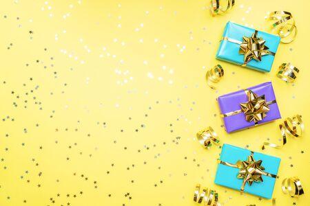 有金丝带和弓的礼物盒,在黄色背景的五彩纸屑星。复制空间平的位置贺卡为生日聚会,圣诞节婚礼母亲节。